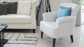 white and blue pillows on a white leather couch in vintage living room